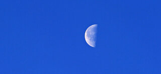 Skull of the Moon Against Sky Blue
