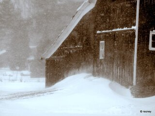 Snow drifts against the barn